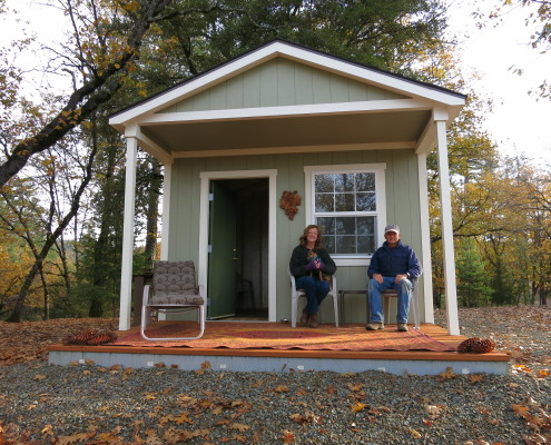 Kristi and Wayne relaxing on the porch of the completed Cabin.